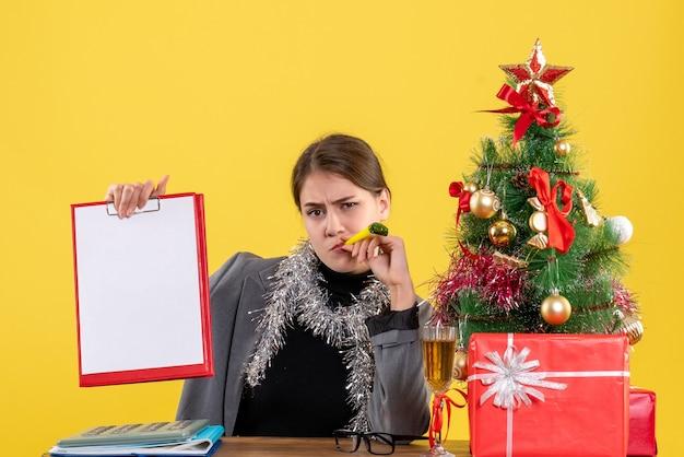 Vue avant réfléchie fille assise à la table tenant le document avec arbre de noël de la couronne et cocktail de cadeaux