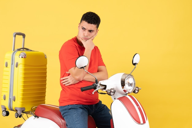 Vue avant réfléchie jeune homme dans des vêtements décontractés sur cyclomoteur