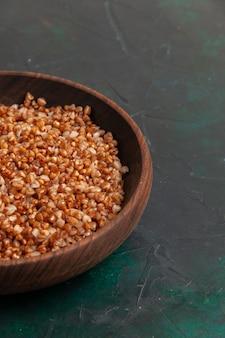 Vue avant repas savoureux de sarrasin cuit à l'intérieur de la plaque brune sur la surface vert foncé
