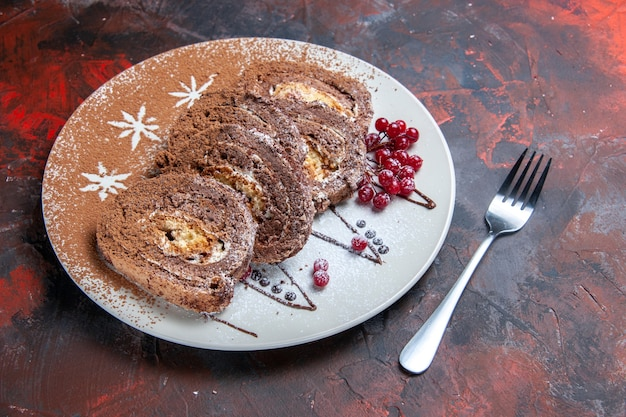 Vue avant des rouleaux de biscuits sucrés en tranches de gâteaux crémeux sur le plancher sombre gâteau à tarte sucré