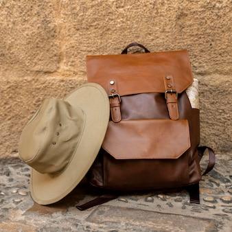 Vue avant sac à dos et chapeau au sol