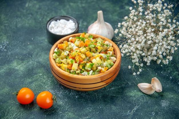 Vue avant de la salade de légumes bouillis mélangés à l'intérieur de la plaque ronde sur fond sombre