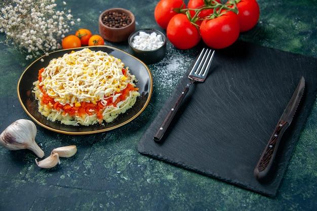 Vue avant de la salade de mimosa à l'intérieur de la plaque avec des assaisonnements et des tomates rouges sur la surface bleu foncé photo cuisine anniversaire de vacances cuisine couleur repas