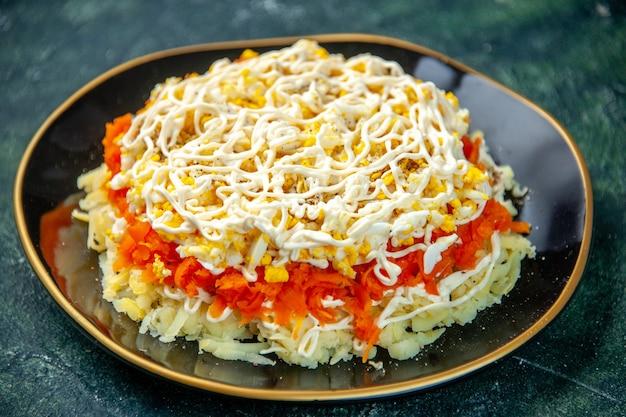 Vue avant salade mimosa avec des oeufs de pommes de terre et de poulet à l'intérieur de la plaque sur la surface bleu foncé vacances anniversaire nourriture repas photo cuisine cuisine couleur