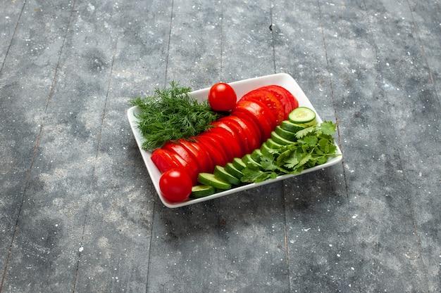 Vue avant de la salade de tomates fraîches en tranches élégamment conçu sur l'espace gris