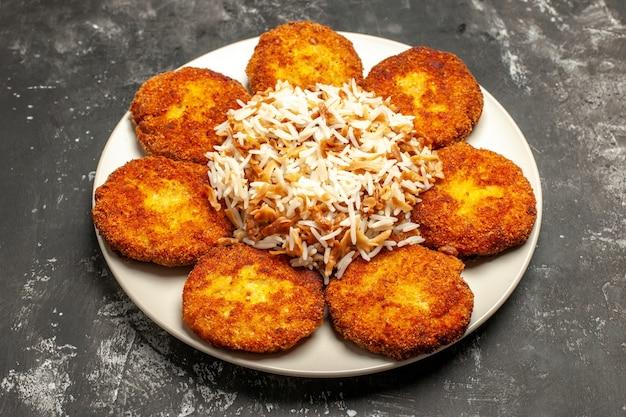 Vue avant de savoureuses côtelettes frites avec du riz cuit sur une surface sombre photo repas plat de viande