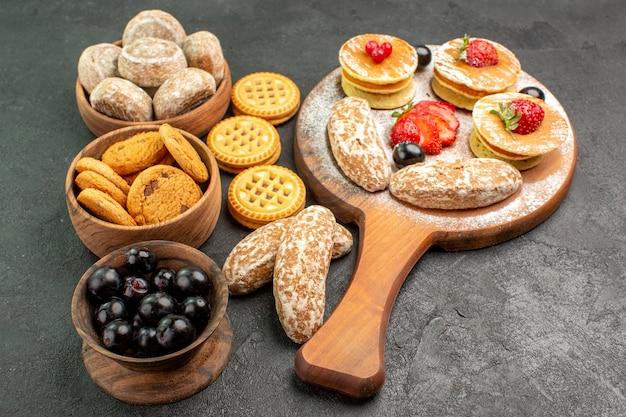 Vue avant de savoureuses crêpes avec des gâteaux sucrés et des fruits sur la surface sombre dessert gâteau sucré