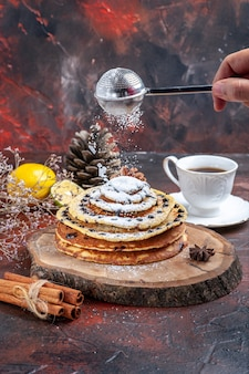 Vue avant de savoureuses crêpes sucrées avec du sucre en poudre sur fond sombre