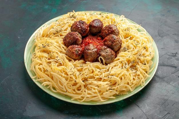 Vue avant de savoureuses pâtes italiennes avec des boulettes de viande sur une surface bleue
