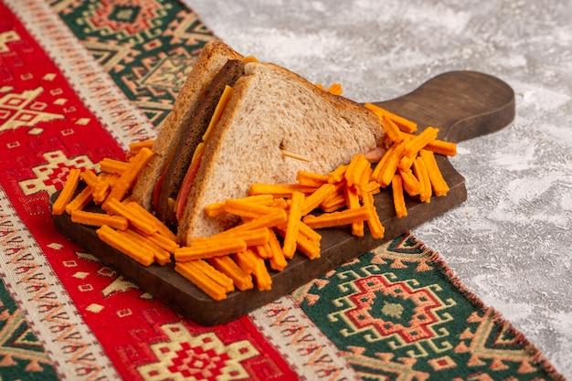 Vue avant de savoureux sandwich au pain grillé avec jambon au fromage avec frites sur blanc