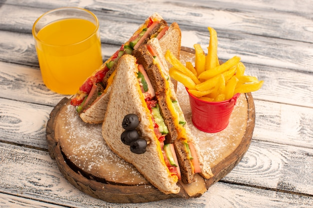 Vue avant de savoureux sandwichs au pain grillé avec du jambon au fromage à l'intérieur avec du jus de frites sur bois