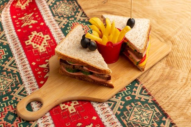 Vue avant de savoureux sandwichs avec tomates jambon d'olive avec frites sur woode