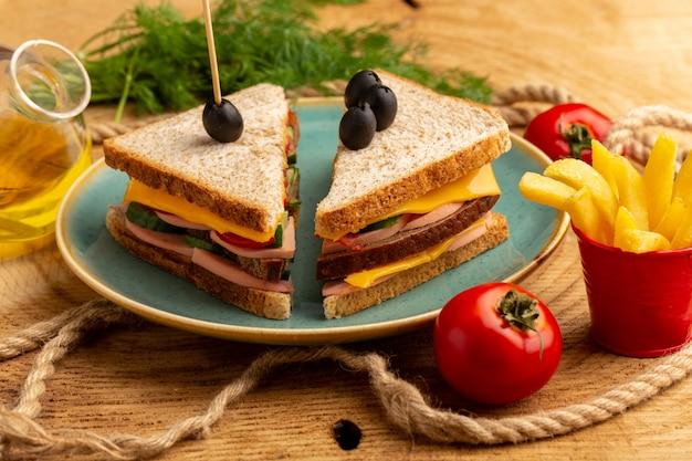 Vue avant de savoureux sandwichs avec tomates jambon olive à l'intérieur de la plaque avec frites tomates à l'huile sur bois