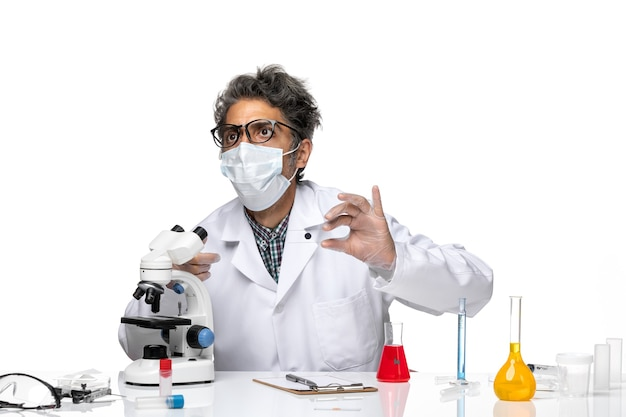 Vue avant scientifique d'âge moyen en costume médical blanc contrôle petit échantillon au microscope