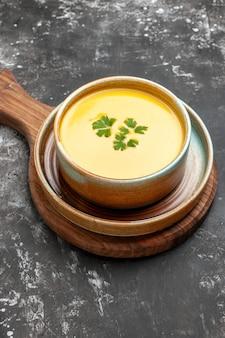 Vue avant de la soupe à la citrouille à l'intérieur de la plaque sur la table sombre