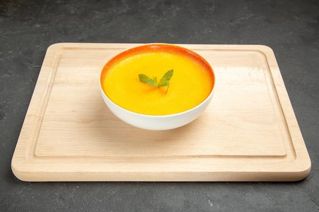 Vue avant de la soupe à la citrouille savoureuse à l'intérieur de la plaque sur la couleur de la soupe de bureau léger