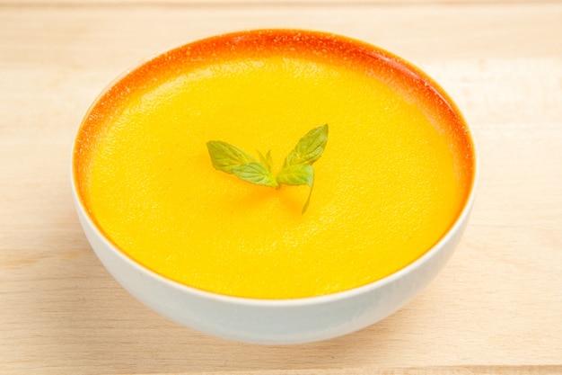 Vue avant de la soupe à la citrouille savoureuse à l'intérieur de la plaque sur la couleur de la soupe