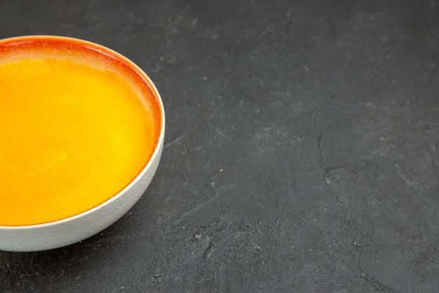 Vue avant de la soupe à la citrouille simple à l'intérieur de la plaque sur un bureau gris