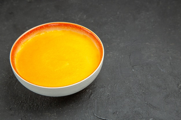 Vue avant de la soupe à la citrouille simple à l'intérieur de la plaque sur la table grise