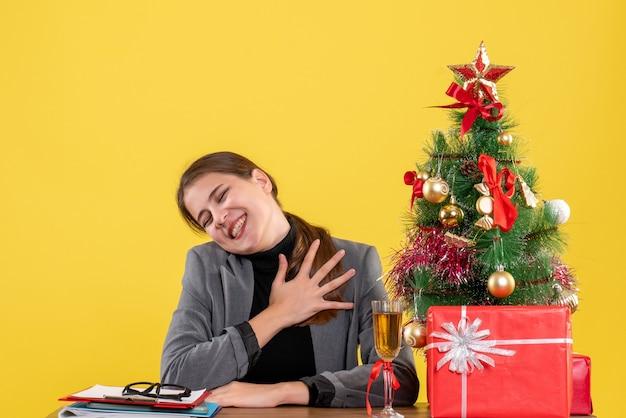Vue avant sourit fille assise au bureau mettant la main à la poitrine arbre de noël et cadeaux cocktail