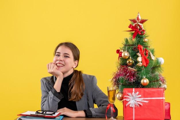 Vue avant sourit fille assise au bureau mettant la main à son arbre de noël de la mâchoire et des cadeaux cocktail