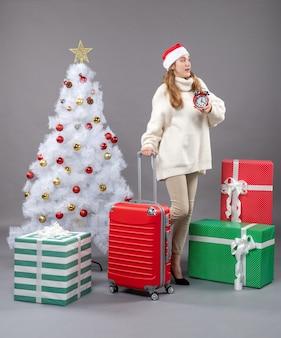 Vue avant surpris fille blonde avec bonnet de noel tenant un réveil rouge près de l'arbre de noël blanc et présente