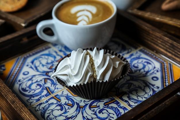 Vue avant de la tasse de cappuccino avec meringue sur un plateau