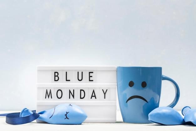 Vue avant de la tasse avec froncement de sourcils et boîte à lumière pour le lundi bleu