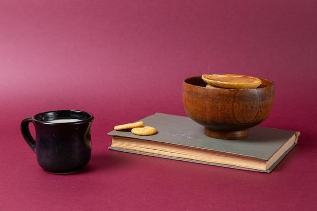 Vue avant de la tasse de tasse de lait noir avec des crêpes sur la surface violette