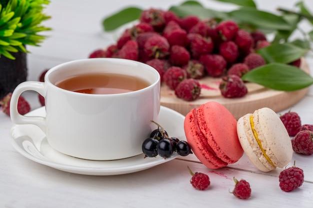 Vue avant de la tasse de thé avec macaron et framboises sur une surface blanche