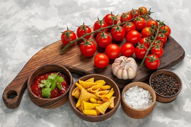 Vue avant des tomates cerises fraîches avec différents assaisonnements sur la surface blanche de l'usine de salade de légumes repas alimentaire