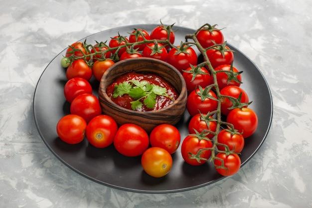 Vue avant des tomates cerises fraîches à l'intérieur de la plaque avec sauce tomate sur la surface blanche salade de légumes repas nourriture santé
