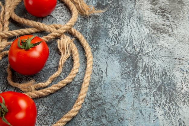Vue avant des tomates rouges fraîches avec des cordes