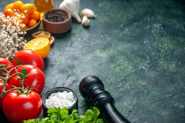 Vue avant des tomates rouges fraîches avec des kumquats sur la surface sombre couleur salade repas repas régime alimentaire santé poivre
