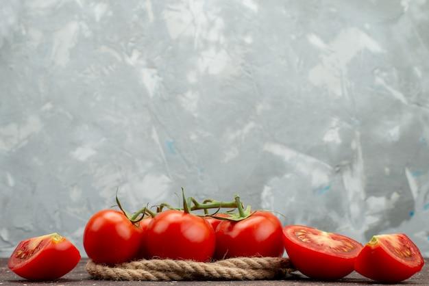Vue avant de tomates rouges fraîches mûres et entières en tranches sur blanc, avec des cordes couleur alimentaire de fruits légumes berry