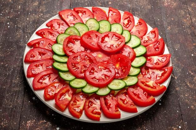 Vue avant de tomates rouges fraîches en tranches de salade fraîche sur espace brun