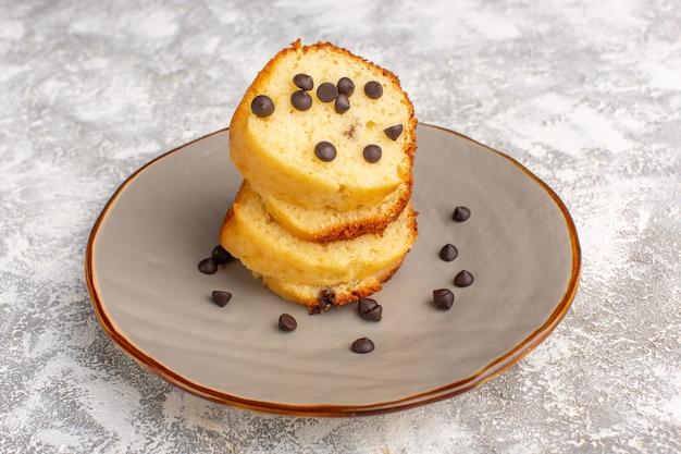 Vue avant de la tranche de gâteau à l'intérieur de la plaque avec des chips de chocolat sur le bureau léger