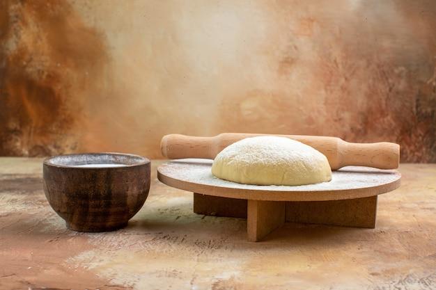 Vue avant de la tranche de pâte crue avec de la farine sur la cuisine de plat de pâtes bureau crème