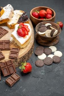 Vue avant des tranches de gâteau avec des barres de chocolat et des cookies sur fond gris