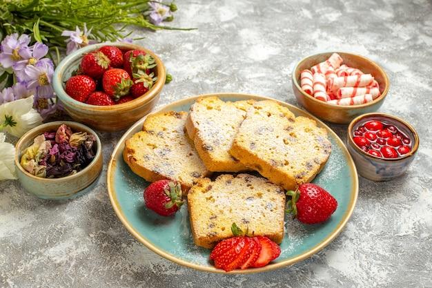 Vue avant des tranches de gâteau délicieux avec des fraises et des bonbons sur une surface légère de tartes au gâteau sucré