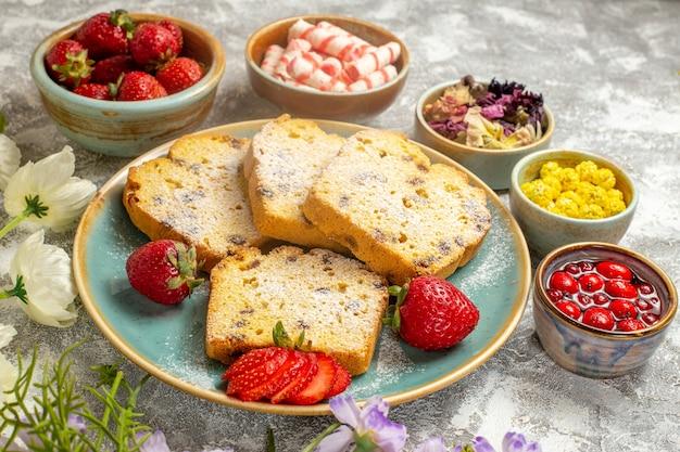 Vue avant des tranches de gâteau délicieux avec des fruits sur la surface légère gâteau à tarte aux fruits sucré