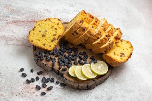 Vue avant des tranches de gâteau délicieux avec des raisins secs et des tranches de citron sur une surface blanche