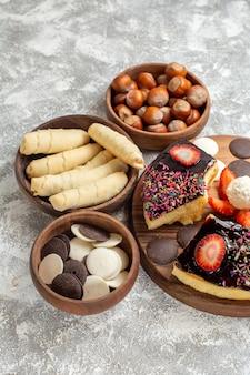 Vue avant des tranches de gâteau avec des noix de biscuits et des bonbons sur fond blanc