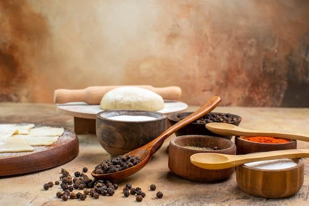Vue avant des tranches de pâte crue avec des assaisonnements sur le plat de bureau crème pâtes repas