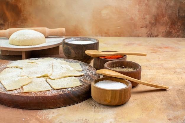 Vue avant des tranches de pâte crue avec de la farine et des assaisonnements sur le plat de bureau crème pâtes cuisine