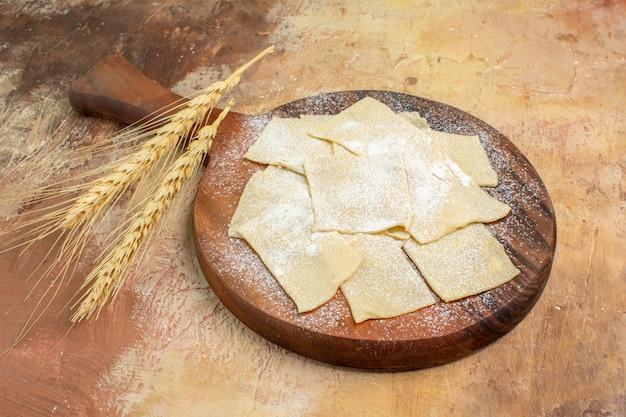 Vue avant des tranches de pâte crue avec de la farine sur le bureau de la crème