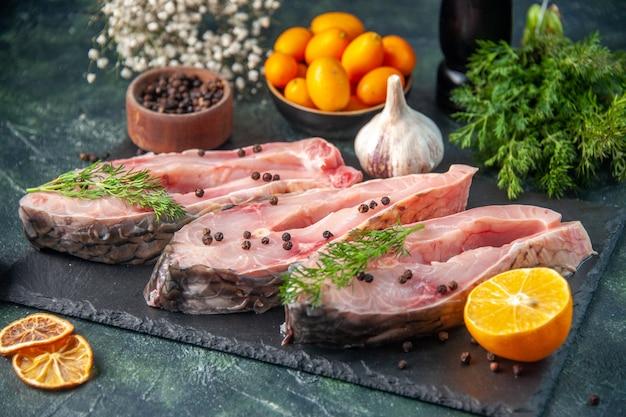 Vue avant des tranches de poisson frais avec du poivre sur la surface sombre de la viande de l'océan repas cru de l'eau photo couleur dîner
