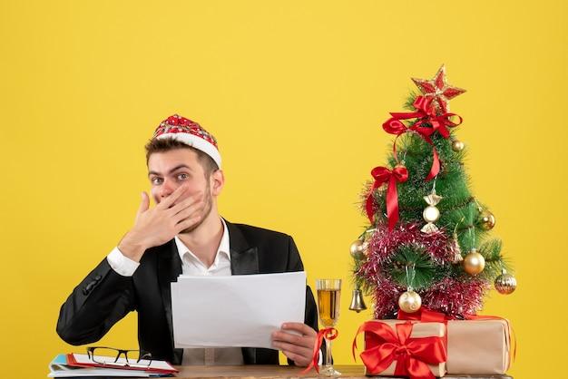 Vue avant travailleur masculin assis derrière son lieu de travail tenant des documents sur le bureau jaune nouvel an travail couleur de bureau noël