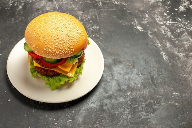 Vue avant de la viande savoureuse hamburger avec des légumes sur la surface grise sandwich pain de restauration rapide