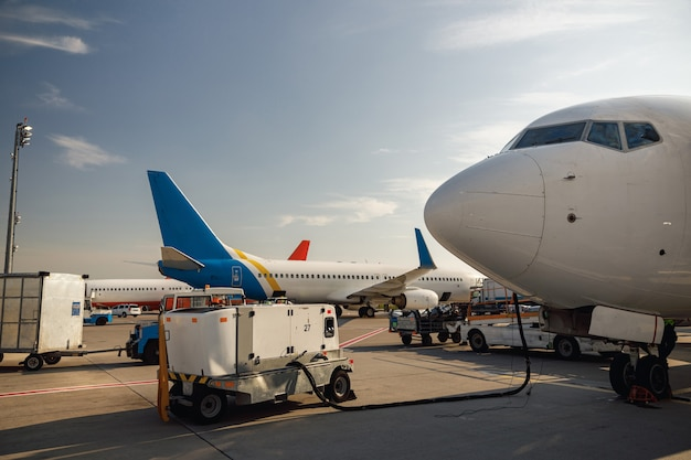 Vue de l'avion blanc pendant le ravitaillement à l'aéroport à l'extérieur pendant la journée. détails de l'avion. avion, expédition, concept de transport